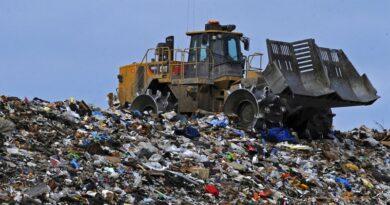 Bagr třídící hromady odpadu